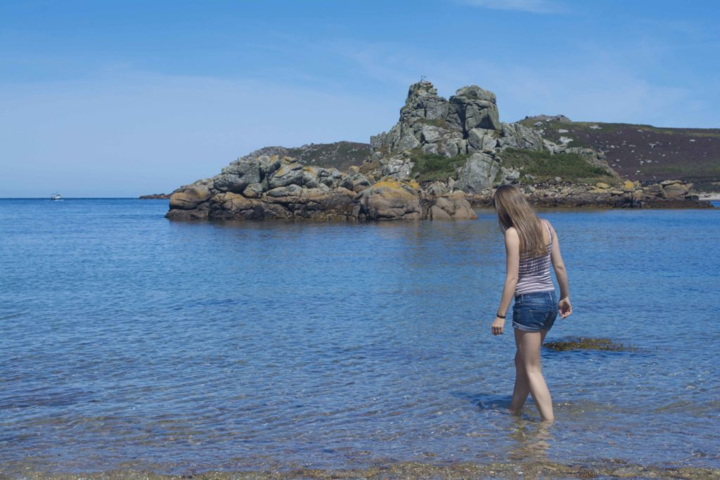 Young woman paddling in the sea off Bryher Isles of Scilly