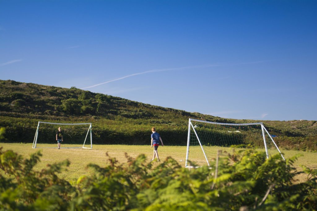 Teenagers playing football on the games field at Bryher Campsite Isles of Scilly