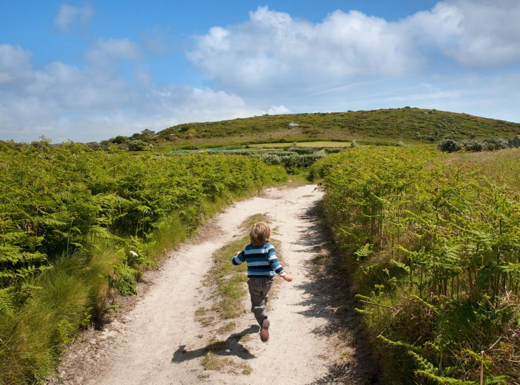 Boy running up a country track on Bryher, Isles of Scilly, Cornwall, England.