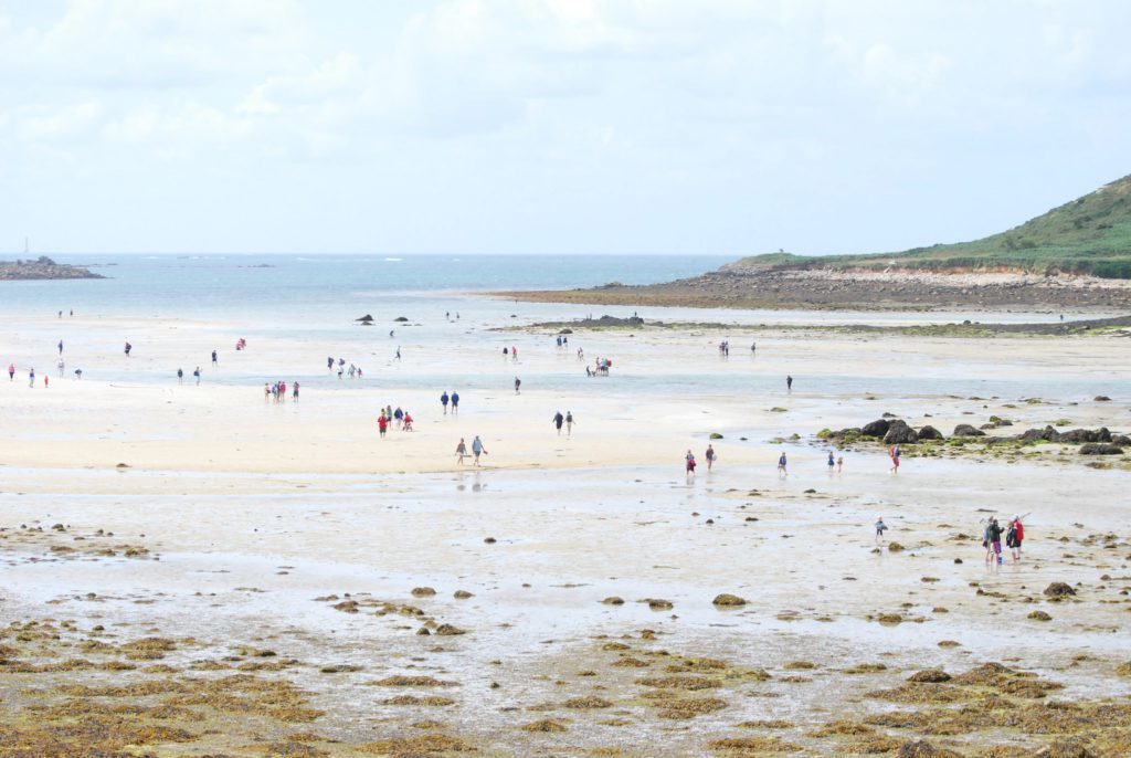 People walking across the channel between Tresco and Bryher on the Isles of Scilly at low tide