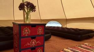 Bryher Campsite Bell Tents include cosy touches like a rag rug and a chest of drawers